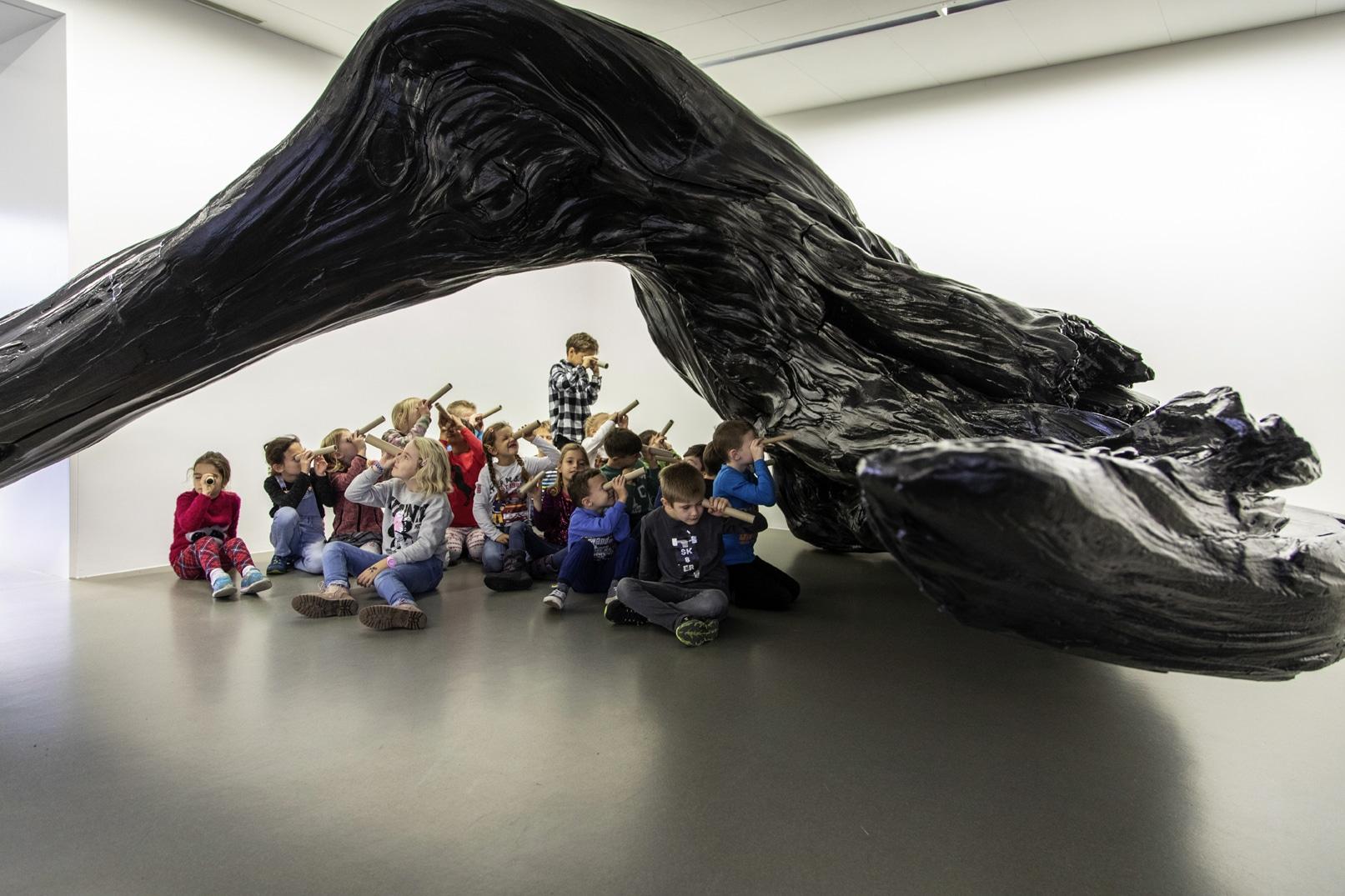 Schülergruppe unter Wurzel mit Kartonröhre am Erforschen_Kunstvermittlung