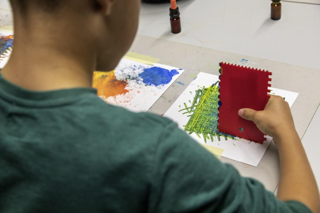 Kind mit Leimschaber am Malen_Kunstvermittlung